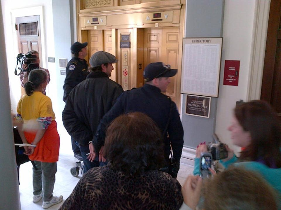 This handout photo provided by NationalADAPT shows handcuffed actor Noah Wyle, center, on Capitol Hill in Washington Monday, April 23, 2012.  Wyle and more than 100 members of the group ADAPT were arrested during a Capitol Hill protest to urge Congress not to cut Medicaid. (AP Photo/NationalADAPT)