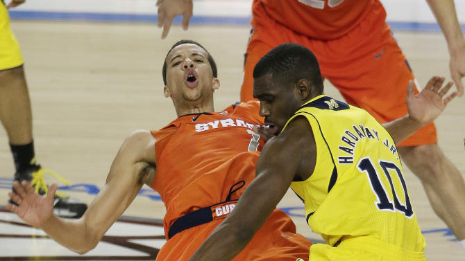 Syracuse's Michael Carter-Williams (1) falls to the court as Michigan's Tim Hardaway Jr. (10) vies for  the ball during the second half of the NCAA Final Four tournament college basketball semifinal game Saturday, April 6, 2013, in Atlanta. (AP Photo/Chris O'Meara)