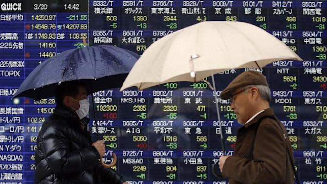 Pedestrians holding umbrellas walk past an electronic board showing stock prices outside a brokerage in Tokyo