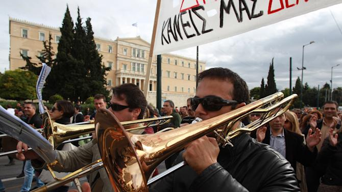 Members of Athens municipal brass band play their instruments during a protest in front of the Greek parliament on Tuesday, Nov. 20, 2012. About 2,500 people took part in the protest, against government plans to place 2,000 civil servants on notice ahead of reassignment or potential dismissal. Greece faces a tense wait Tuesday for vital bailout money as finance ministers from the 17 European Union countries that use the euro try to reach an agreement on how to put the country's economic recovery back on the right track. (AP Photo/Thanassis Stavrakis)