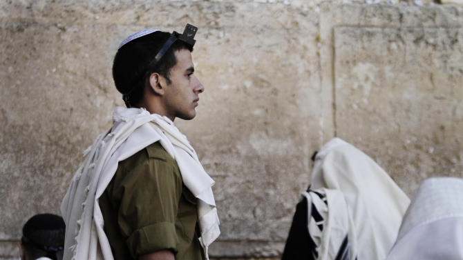 An Israeli soldier prays next to the Western Wall, the holiest site where Jews can pray, in Jerusalem's Old City. Monday, July 2, 2012. Israel's prime minister on Monday dissolved a high-profile committee assigned to reform the country's military draft law to spread the burden among more sectors of society, conscripting ultra-Orthodox Jews and requiring Israeli Arabs to do civilian service. (AP Photo/Dan Balilty)