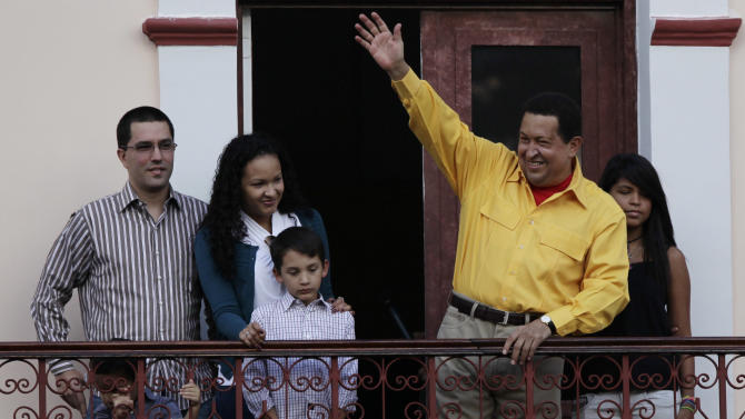Accompanied by relatives, Venezuela's President Hugo Chavez, second from right, waves to supporters from a balcony of Miraflores presidential palace in Caracas, Venezuela, Thursday, July 28, 2011. Chavez sang on a balcony of the presidential palace as he celebrated his 57th birthday before a crowd of supporters, vowing to overcome cancer. (AP Photo/Ariana Cubillos)