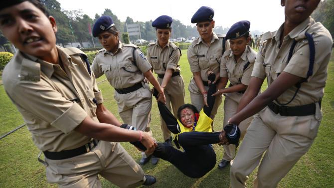 Indian policemen detain a Tibetan Youth Congress (TYC) supporter as she protests outside the Chinese Embassy in New Delhi, India, Monday, Nov. 12, 2012. TYC supporters shouted anti-Chinese government slogans outside the embassy to show support to Tibetans inside China who have set themselves on fire and protested against the Chinese government. (AP Photo/Saurabh Das)