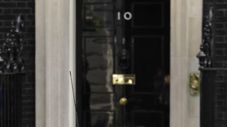 British Prime Minister David Cameron looks out from a BMW Mini Cooper S outside 10 Downing Street in London, Thursday, June 9, 2011. BMW announced Thursday an investment to built the next generation of Mini cars in their Cowley factory in England. (AP Photo/Sang Tan)
