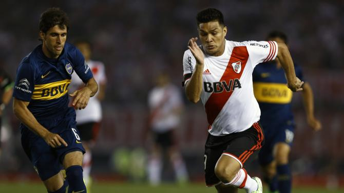 Boca Juniors' Juan Forlin and River Plate's Teofilo Gutierrez run for the ball during their Copa Sudamericana second leg semi-final soccer match in Buenos Aires