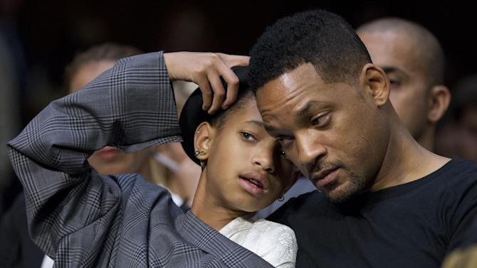 Actor Will Smith, and his daughter Willow Camille Reign Smith, accompanying Jada Pinkett Smith, not in picture, testifying in a Senate Foreign Relations Committee hearing about human trafficking, communicate in whisper, on Capitol Hill in Washington Tuesday, July 17, 2012.  (AP Photo/Manuel Balce Ceneta)