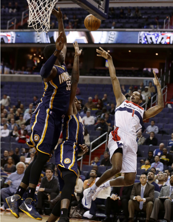 Washington Wizards forward Trevor Ariza shoots over Indiana Pacers center Roy Hibbert, left, and forward Paul George in the first half of an NBA basketball game Monday, Nov. 19, 2012, in Washington. (