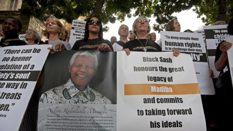 Members of the Black Sash human rights organisation gather together in silent tribute to former South African President Nelson Mandela on the steps of St. George's Cathedral in Cape Town