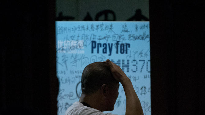"One of the relatives of Chinese passengers on board Malaysia Airlines Flight 370 rubs his head near a board covered with written wishes from relatives during a briefing given by Malaysian officials at a hotel in Beijing, China, Wednesday, March 26, 2014. Some of the wishes, partially seen, read, ""Dear husband, you must stay strong, I am waiting for you. My dear, please be back soon."" The search for the missing plane resumed Wednesday after fierce winds and high waves forced crews to take a break Tuesday. (AP Photo/Alexander F. Yuan)"