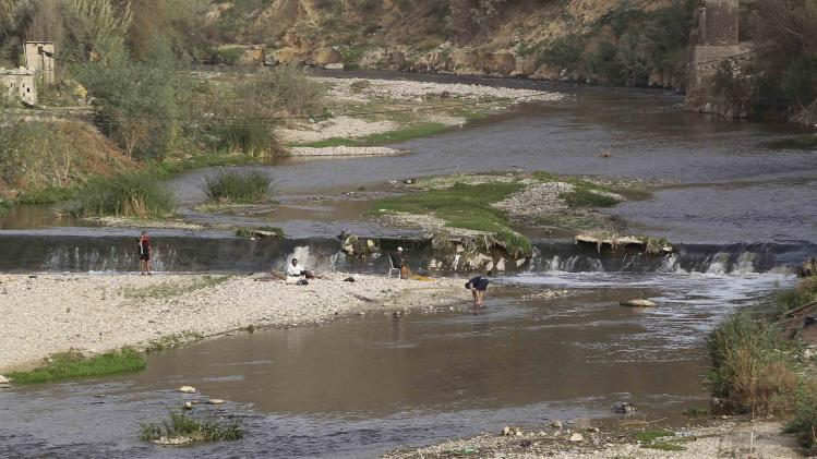 People fish in the Jerash water stream, which flows into the King Talal Dam, near Jerash