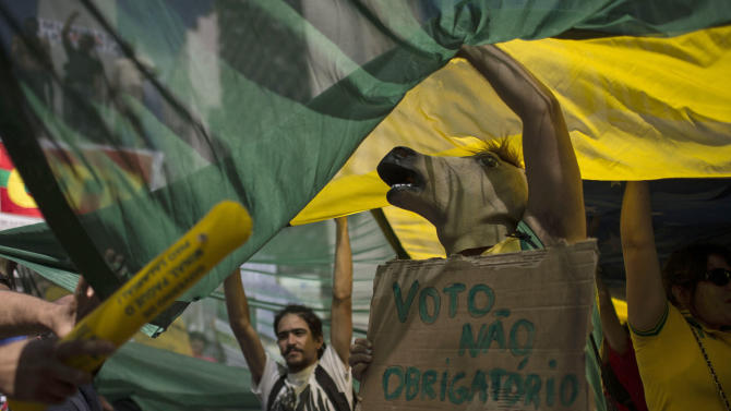 """A masked demonstrator holds a sign that reads in Portuguese """"No mandatory vote,"""" referring to Brazil's law that citizens are obligated to vote in all elections, during a march toward the Mineirao stadium where a Confederations Cup semifinal soccer match will be played between Brazil and Uruguay in Belo Horizonte, Brazil, Wednesday, June 26, 2013. The wave of protests that hit Brazil on June 17 began as opposition to transportation fare hikes, then expanded to a list of causes including anger at high taxes, poor services and high World Cup spending, before coalescing around the issue of rampant government corruption. (AP Photo/Felipe Dana)"""