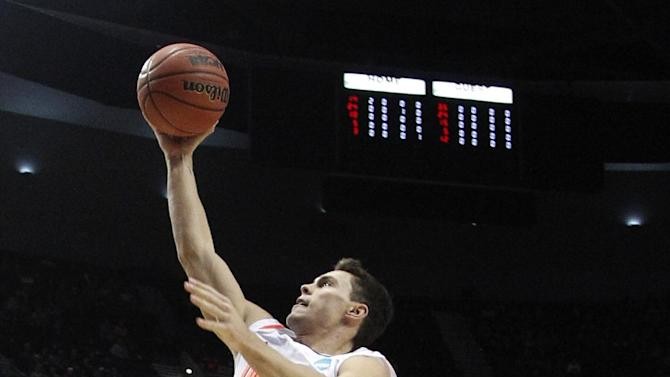 Louisville's Kyle Kuric (14) goes to the basket as Davidson's Nik Cochran (12) looks on during the first half of an NCAA tournament second-round college basketball game in Portland, Ore., Thursday, March 15, 2012. (AP Photo/Rick Bowmer)
