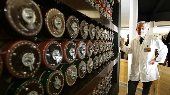 FILE This Tuesday, March 24, 2009 file photo shows Mike Hillyard, one of the volunteers who rebuilt a replica of the Turing Bombe machine that played a crucial part in cracking the Nazi Enigma Code, standing by the machine at Bletchley Park in Milton Keynes, England. The British government is recruiting apprentice spies and codebreakers without university degrees in a bid to deepen the talent pool of its intelligence services. Foreign Secretary William Hague will announce details Thursday Oct. 18, 2012 in a speech at Bletchley Park, Britain's World War II code-breaking headquarters.  (AP Photo/Akira Suemori)