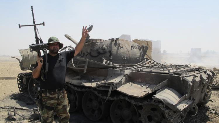 An Iraqi Shiite militia fighter flashes the victory sign after breaking a long siege of Amerli by Islamic State militants