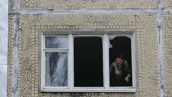 A woman looks out of the window of a residential block damaged by a shelling in Donetsk, eastern Ukraine