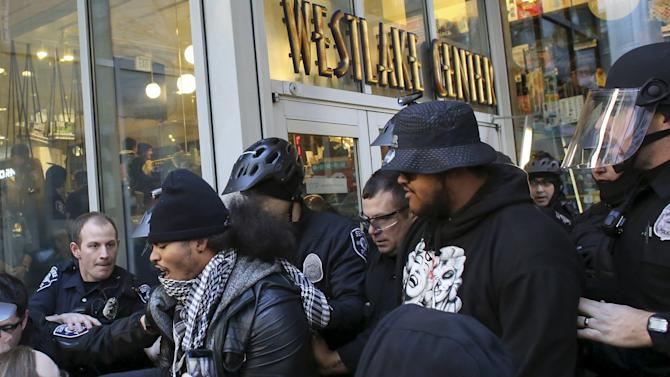 Police scuffle with Black Lives Matter protesters while attempting to close an entrance to Westlake Mall on Black Friday in Seattle, Washington