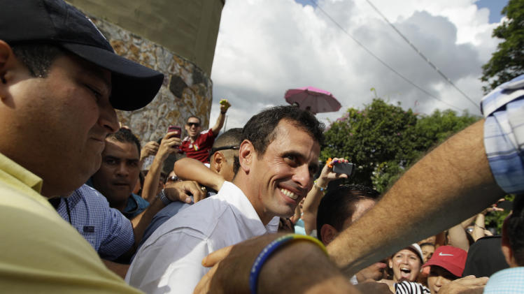 Opposition presidential candidate Henrique Capriles greets supporters as he leaves a polling station after voting in the presidential election in Caracas, Venezuela, Sunday, Oct. 7, 2012. Capriles is running against President Hugo Chavez. (AP Photo/Ariana Cubillos)