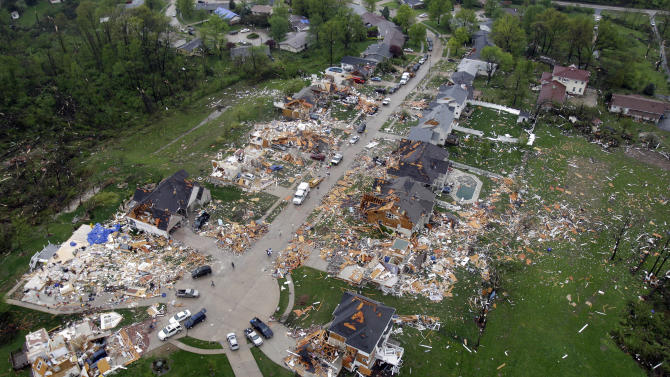 In this aerial photograph, debris is strewn about a neighborhood Saturday, April 23, 2011, in Bridgeton, Mo., following a Friday-evening tornado in the area. St. Louis' main airport was closed for business Saturday while crews cleaned up after a tornado tore through a terminal, causing several injuries and sending people scurrying for shelter as plated glass shattered around them. (AP Photo/Jeff Roberson)