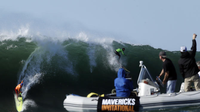 Spectators cheer on Nathan Fletcher, left, and Rusty Long as they compete during a semifinal heat at the Mavericks Invitational big wave surf contest in Half Moon Bay, Calif., Sunday, Jan. 20, 2013. (AP Photo/Marcio Jose Sanchez)