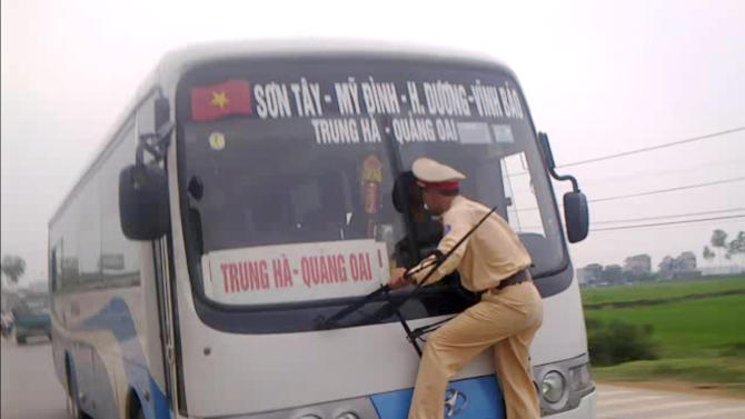 In this photo made from a video filmed Monday, April 9, 2012 and released by Hanoi Police, Vietnamese traffic police 2nd Lt. Nguyen Manh Phan clings on to the windshield wipers of a moving bus as he goes on a wild ride for nearly a kilometer (0.62 miles) after the rogue driver tried to avoid a ticket in Ba Vi District outside Hanoi, Vietnam. Phan ordered the bus driver to pull over the 39-seat passenger coach but the driver allegedly refused to show his paperwork and drove off, but not before Phan leaped onto the front. The driver eventually pulled over after being chased by police and residents. Even with the bus stopped, Phan stood calmly in front of it, still hanging on to the wipers. (AP Photo/Hanoi Police)
