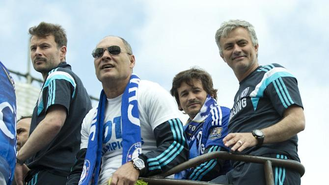 Chelsea's head coach Jose Mourinho, right, sits on the open top bus as the team parade through the streets near their Stamford Bridge stadium, in London Monday, May 25, 2015. Chelsea won the English Premier League title for 2014/15 as well as the League Cup, with both trophies on display. (AP Photo/Alastair Grant)