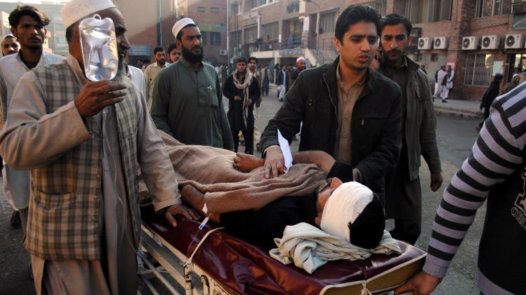 People care for a person injured in a blast on Monday, Dec. 3, 2012 in Peshawar, Pakistan. A bomb ripped through a police van as it was patrolling in northwestern Pakistan on Monday, killing several officers and wounding others, police said. (AP Photo/Mohammad Sajjad)