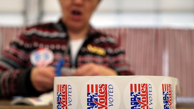 "An electoral official prepares ""I Voted"" stickers as local residents vote at a fire station in Loudon, New Hampshire, on February 9, 2016"