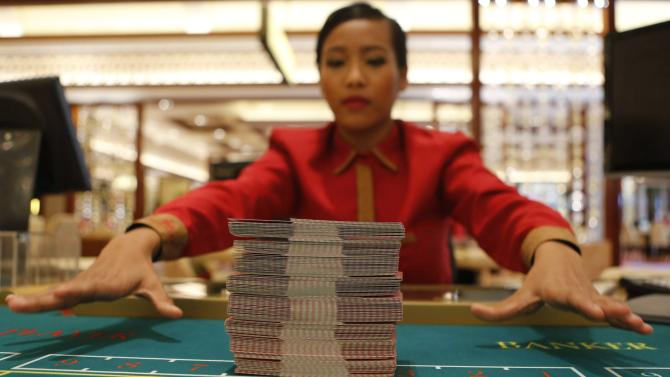 File photo of a Solaire Casino-Resort dealer practicing her card skills on a baccarat table a few days before the casino's opening in Pasay city, Metro Manila