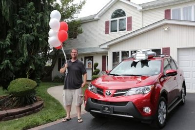 Toyota's 50 millionth customer and NYPD vet Michael Dee stands beside his brand-new 2013 RAV4
