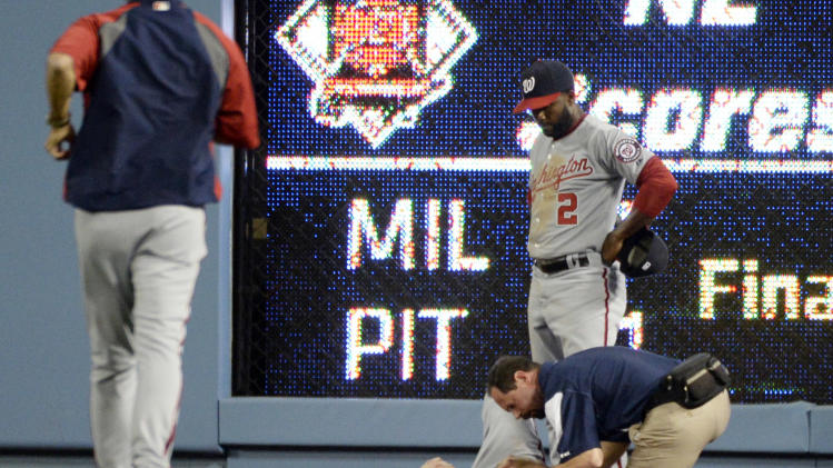 May 13, 2013; Los Angeles, CA, USA; Medical personnel look after an injured Washington Nationals left fielder Bryce Harper (34) after he collided with the scoreboard during the fifth inning against the Los Angeles Dodgers at Dodger Stadium. (Richard Mackson-USA TODAY Sports)