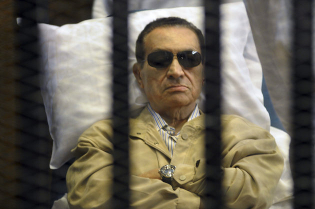FILE - In this June 2, 2012 file photo, Egypt's ex-President Hosni Mubarak lays on a gurney inside a barred cage in the police academy courthouse in Cairo, Egypt. Ousted President Hosni Mubarak watched the uprising against him unfold through a live TV feed, despite his earlier denial that he knew the extent of the protests and violence, according to a fact-finding mission member said Wednesday, Jan. 2, 2013, which could lead to the retrial of the 84-old ousted leader already serving a life sentence.(AP Photo/File)