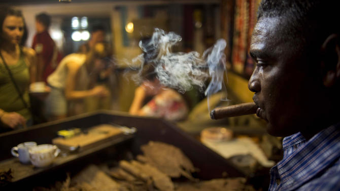 A worker rolls cigars during a demonstration for tourists at a cigar club shop in Havana, Cuba, Friday, Dec. 19, 2014. Cigars brought back to the U.S. must be for personal use, not resale - same as the rules that existed for travelers before August 2004, when the Bush administration imposed strict restrictions those traveling to the island. (AP Photo/Ramon Espinosa)