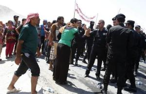 A displaced woman from the minority Yazidi sect argues with Kurdish security during a demonstration in Zakho district