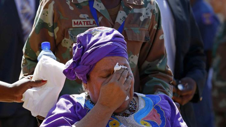 A woman cries after paying her respects at the coffin of former South African President Nelson Mandela, as Mandela lies in state at the Union Buildings in Pretoria