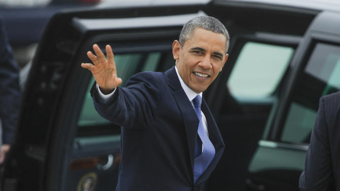 President Barack Obama waves to a crowd gathered at Hartsfield-Jackson International Airport on his way to give the commencement speech at Morehouse College, Sunday, May 19, 2013, in Atlanta. (AP Photo/John Amis)