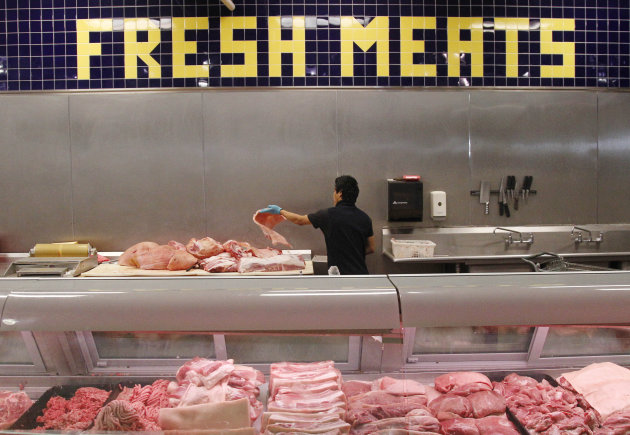 Butcher Freddie Quina cuts meat at Super Cao Nguyen in Oklahoma City, Wednesday, July 25, 2012. The record drought gripping half the country will help push food prices up by 3 percent to 4 percent next year, the U.S. Department of Agriculture said. (AP Photo/Sue Ogrocki)