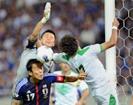 Japan's goalkeeper Eiji Kawashima (top left) and captain Makoto Hasebe (below) fight for the ball with Iraq's Alaa Abdul Zahrah (right) during their World Cup Asian qualifier in Saitama on Tuesday