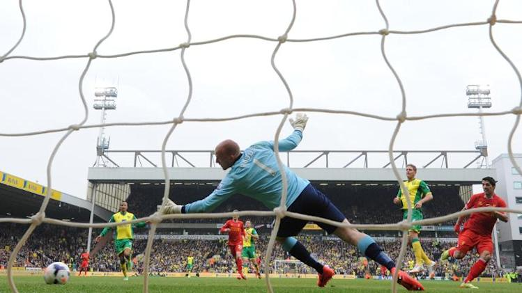 Liverpool striker Luis Suarez (R) shoots to score a goal past Norwich City's English goalkeeper John Ruddy at Carrow Road in Norwich on April 20, 2014