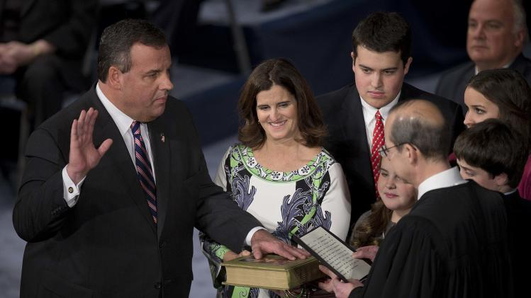 Governor Chris Christie holds his hand aloft as he is sworn in for his second term at the War Memorial Theatre in Trenton