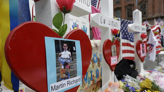 A photo of Martin Richard, 8, hangs at a makeshift memorial near the finish line of Monday's Boston Marathon explosions, which killed at least three and injured more than 140, Thursday, April 18, 2013, in Boston. Richard was killed in the explosions. (AP Photo/Matt Rourke)