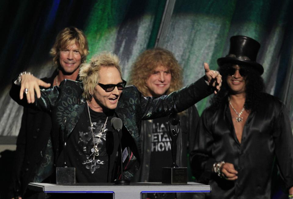 Matt Sorum gestures as Duff McKagan, back left, Steven Adler and Slash, back right, watch, after Guns N' Roses was   inducted into the Rock and Roll Hall of Fame Saturday, April 14, 2012, in Cleveland. (AP Photo/Tony Dejak)