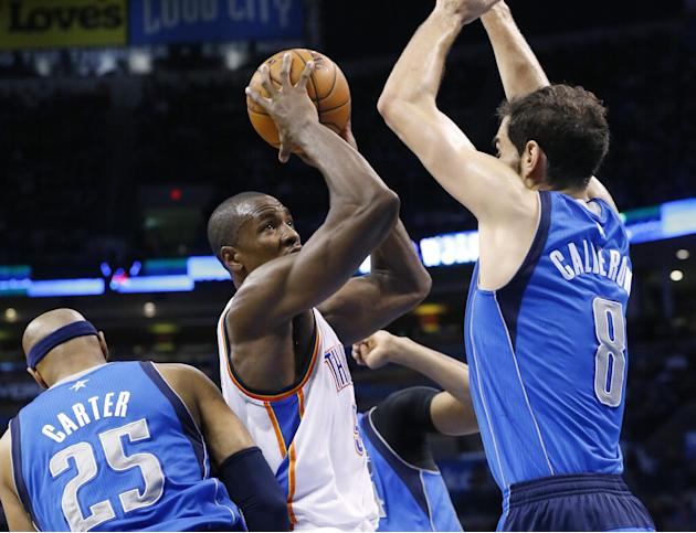 Oklahoma City Thunder forward Serge Ibaka (9) shoots between Dallas Mavericks guard Vince Carter (25) and guard Jose Calderon (8) in the third quarter of an NBA basketball game in Oklahoma City, Sunda