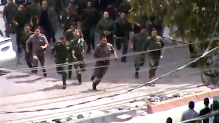This image made from amateur video released by Shaam News Network and accessed Friday, May 25, 2012 purports to show police running toward a protest in Damascus, Syria. (AP Photo/Shaam News Network via AP video) TV OUT, THE ASSOCIATED PRESS CANNOT INDEPENDENTLY VERIFY THE CONTENT, DATE, LOCATION OR AUTHENTICITY OF THIS MATERIAL