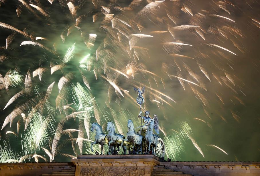 Fireworks explode next to the Quadriga sculpture atop the Brandenburg gate during New Year celebrations in Berlin