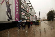 Pedestrians wade across a flooded pavement on a highway linking Athens with its port of Piraeus, during a rainstorm on Friday, Feb. 22, 2013. Hours of heavy rainfall in Athens caused extensive flooding, inundating basements and forcing authorities to close major roads and a central subway station.The Greek fire brigade says it received more than 900 calls to pump out water in the greater Athens region Friday. (AP Photo/Petros Giannakouris)