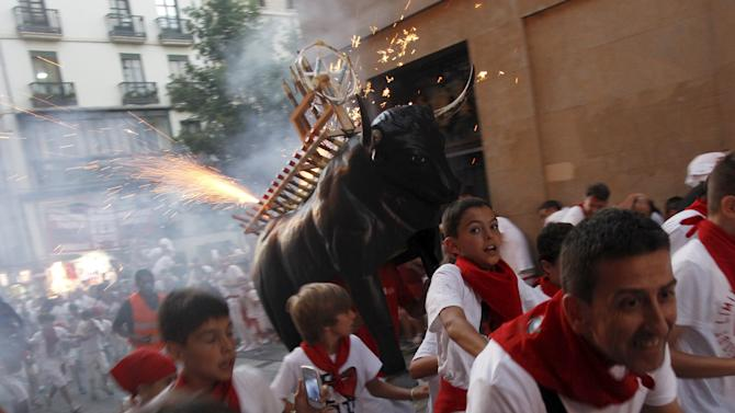 "Revellers run from the ""Fire Bull"" on the second day of the San Fermin festival in Pamplona"