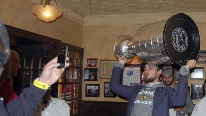 In this photo provided by Harry Caray's Restaurant Group, Chicago Blackhawks' Niklas Hjalmarsson, of Sweden, hoists the Stanley Cup for fans inside Harry Caray's in Rosemont, Ill., Tuesday morning, June 25, 2013, after the team arrived home from Boston following their Stanley Cup hockey final win over the Boston Bruins. (AP Photo/Harry Caray's Restaurant Group)