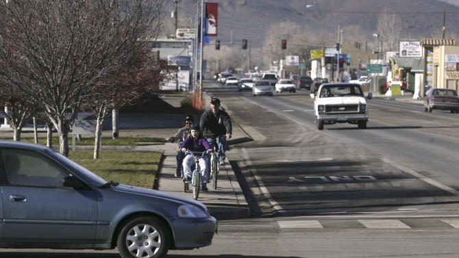 FILE - In this Dec. 12, 2004 file photo, Tom Moore rides through downtown Fernley, Nev., with his daughters, Bridget and Meara. In a reversal of fortunes due to the recent recession, rural America is now losing population, in towns like Fernley, for the first time, because of waning interest among millions of baby boomers in moving to far-flung locations for retirement and recreation. (AP Photo/Cathleen Allison, File)