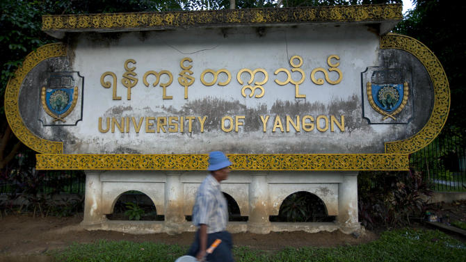 In this picture taken on Saturday, Nov. 17, 2012, a laborer walks past a sign of the University of Yangon, where President Barack Obama is scheduled to deliver a speech on Monday, Nov. 19, 2012, in Yangon, Myanmar.  Since colonial times, the fight for change in Myanmar has begun on this leafy campus. It was a center of the struggle for independence against Britain and served as a launching point for pro-democracy protests in 1962, 1974, 1988 and 1996. For many, the school has today become a symbol of the country's ruined education system and a monument to a half century of misrule. (AP Photo/Gemunu Amarasinghe)