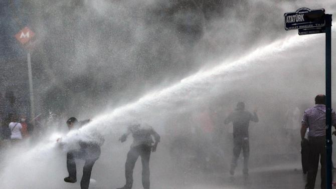 Turkish riot police spray a water cannon at demonstrators in Kizilay Square in Ankara, Turkey, Sunday, June 16, 2013. After authorities evicted activists from an Istanbul park, they are taking a hardline approach against attempts to rekindle protests that have shaken the country. (AP Photo/Burhan Ozbilici)